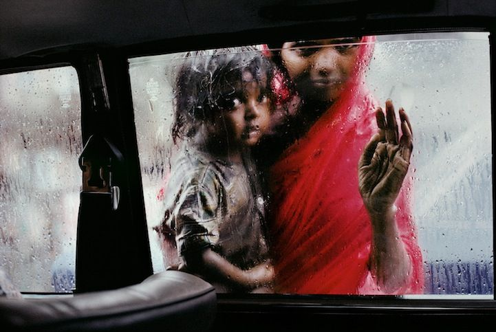 A mother and child beg for alms through a taxi window during the monsoon