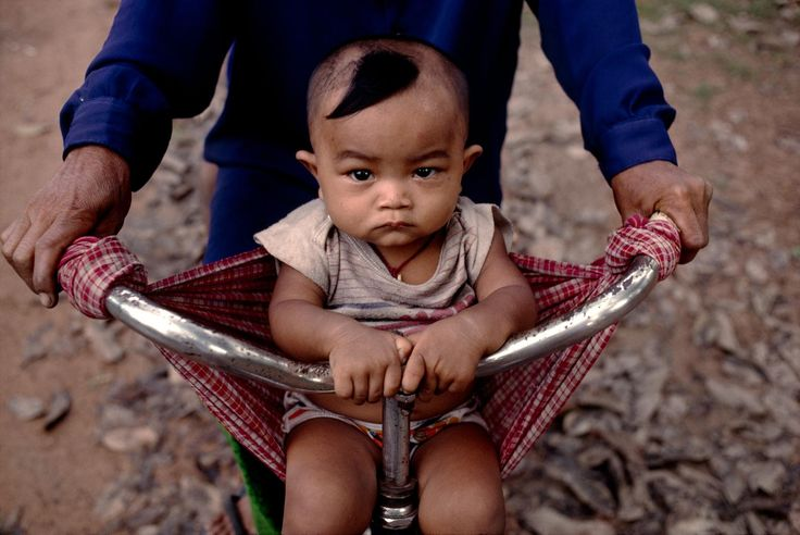 Baby in a bicycle sling, Cambodia